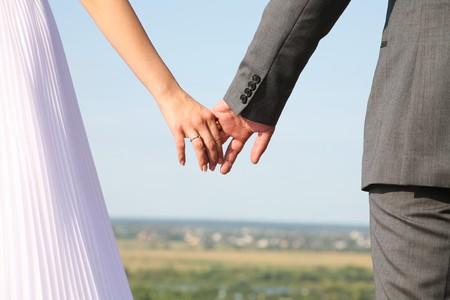 Image of bride and groom holding each other�s hands somewhere outside photo