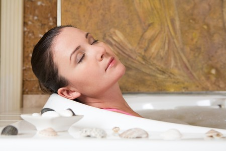 pleasant: Image of relaxing woman with closed eyes having pleasant bath with seashells near by