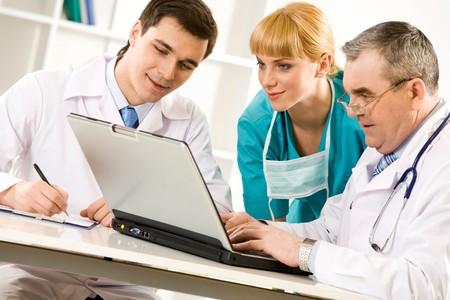 especialistas: Tres especialistas mirando la pantalla port�til mientras anciano escribiendo documento