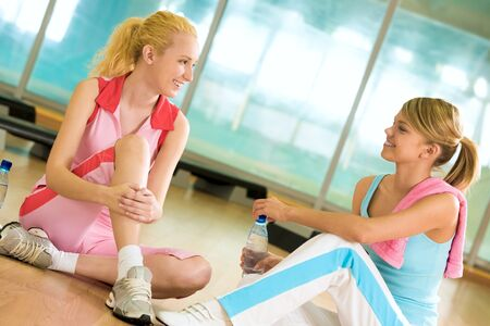 Photo of two girls sitting on the floor of gym and having friendly talk photo