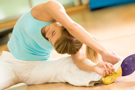 Image of sporty girl sitting on the floor and doing stretching exercise photo