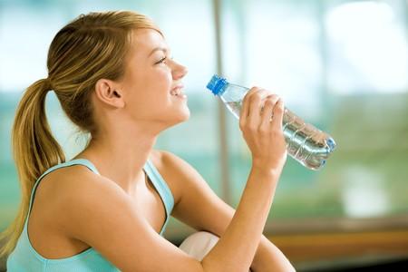 botella de plastico: Perfil de la hermosa mujer va a beber un poco de agua frente botella de pl�stico despu�s de ejercicios Foto de archivo