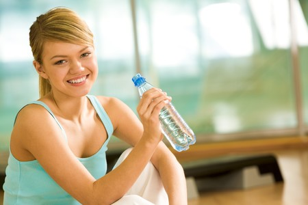 Portrait of lovely girl holding bottle of water in hand and smiling photo