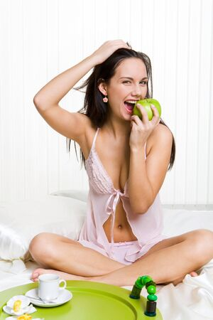 Portrait of healthy woman sitting on bed and eating fresh green apple photo
