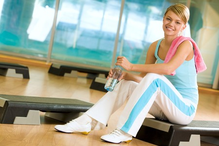 hand holding bottle: Sporty female sitting in the gym with bottle of water in hands and smiling