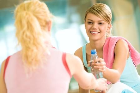 tomando refresco: Chica generosa dando botella de agua al amigo delante de ella