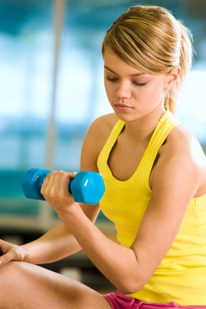 Portrait of young female with dumbbells doing exercises for strong arms Stock Photo - 4549444