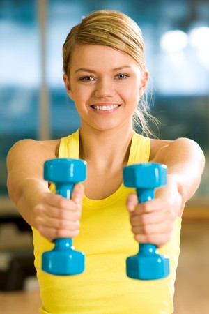 Happy girl stretching her hands with blue dumbbells during workout Stock Photo - 4549460