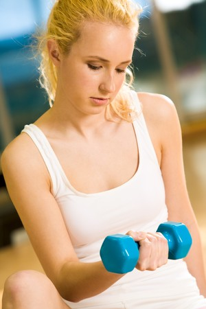 Portrait of strong female doing exercise with dumbbells in sports gym Stock Photo - 4544876