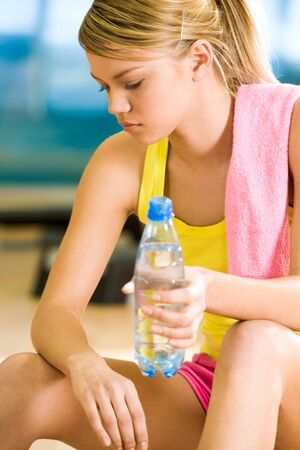 Photo of exerted female having a drink of water after difficult exercises photo