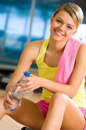 Portrait of happy woman wearing yellow tanktop looking at camera with smile in gym Stock Photo - 4549461