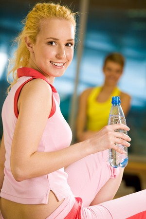 Portrait of cheerful girl holding bottle of water in hand and smiling at camera photo