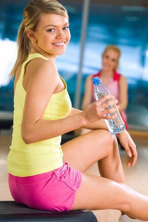 Happy girl sitting on mat with bottle of water in hand and looking at camera with smile Stock Photo - 4549289