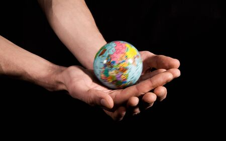 Close-up of human palms with globe model on them over black background photo
