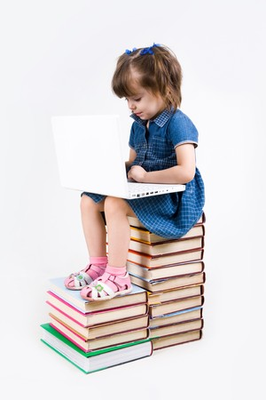 Photo of schoolgirl sitting on books and typing on laptop keyboard