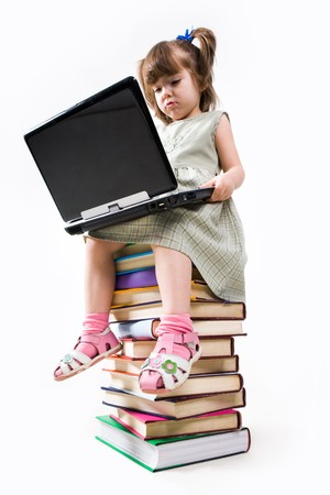 Clever schoolgirl sitting on pile of textbooks and typing on laptop photo