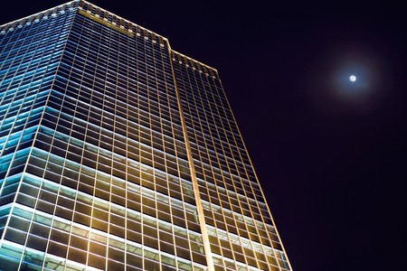View from below of office building at night with full moon in the sky photo