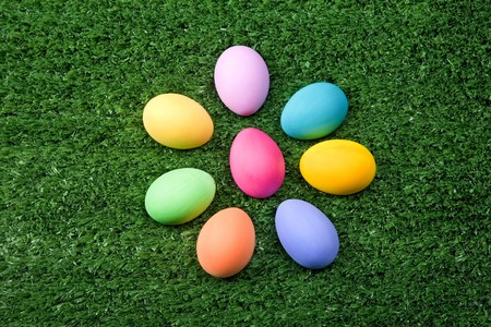 Photo of Easter eggs forming flower shape on green grass  photo
