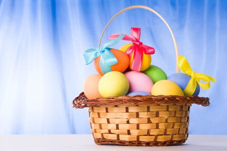 Image of basket full of multicolored Easter eggs over blue background Stock Photo - 4554940