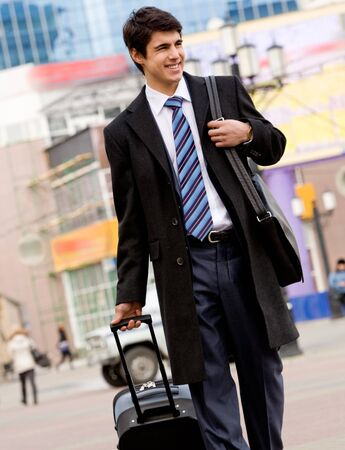 Image of happy guy in suit and coat walking with his baggage and bag Stock Photo