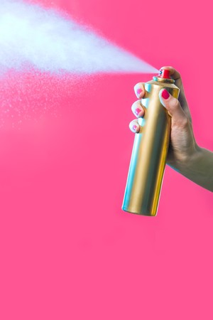 Photo of hair lacquer in female's hand spraying it over red background Stock Photo