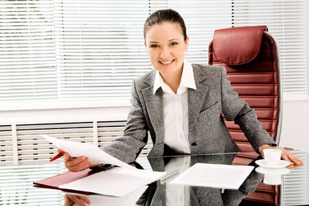 Portrait of happy professional with document in hand looking at camera with smile in office