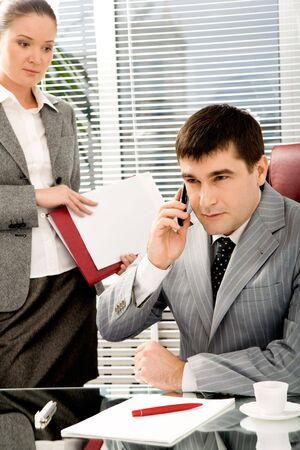 Portrait of confident boss talking on the phone with executive secretary standing near by Stock Photo - 4624748