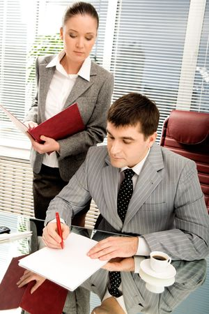 Portrait of serious boss going to sign contract while executive secretary standing near by Stock Photo - 4623398