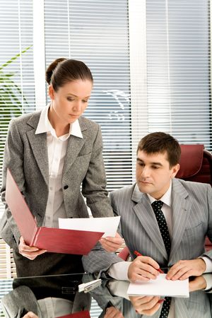 Pretty secretary showing papers to her boss in office Stock Photo - 4623930