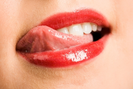 Close-up of female licking her lips by tip of the tongue after eating something delicious Stock Photo - 4624588
