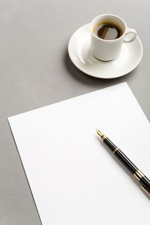 Image of blank paper sheet with penholder on workplace with cup of coffee near by photo