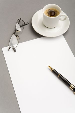 Photo of blank paper sheet with fountain pen, eyeglasses and red cup of coffee near by photo