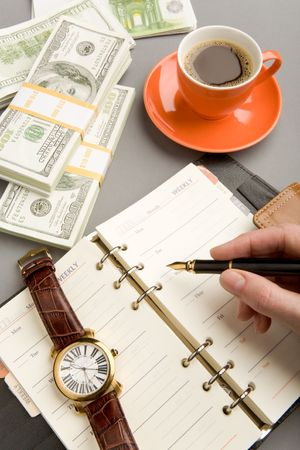 Human hand holding fountain pen ready to write plan on page of notepad with business objects near by Stock Photo - 4623077