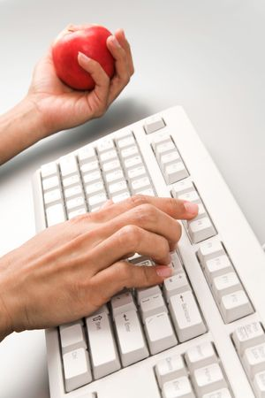 Close-up of female hand pressing buttons of computer keyboard and holding ripe apple at background photo