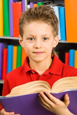Portrait of smart boy with open book looking at camera in library photo