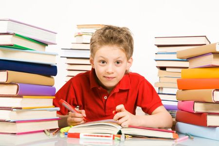 Portrait of cute youngster sitting among stacks of literature with open book in front of him photo
