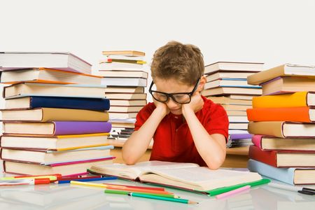 Smart youth in eyeglasses looking into open book before him photo