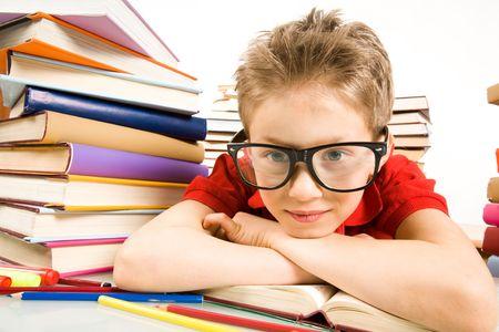 bambini pensierosi: Ritratto di ragazzo pensieroso messa in occhiali la testa sul libro aperto Archivio Fotografico
