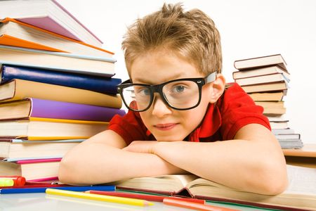 Smart youngster in eyeglasses putting his head on open book and looking at camera photo