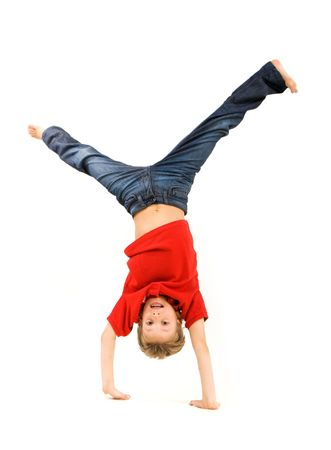 boy barefoot: Playful lad standing on his arms with legs pointing upwards over white background