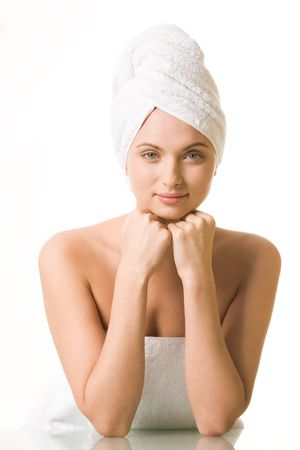 Portrait of pretty female with towel on head touching her face and looking at camera photo