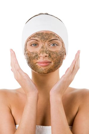 Beautiful woman with purifying facial mask keeping her palms by her face photo