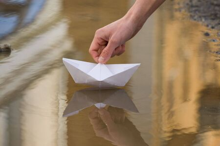 Close-up of human hand putting paper ship lying onto still water photo