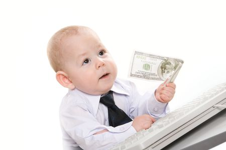Portrait of serious baby boy giving hundred-dollar banknote to someone