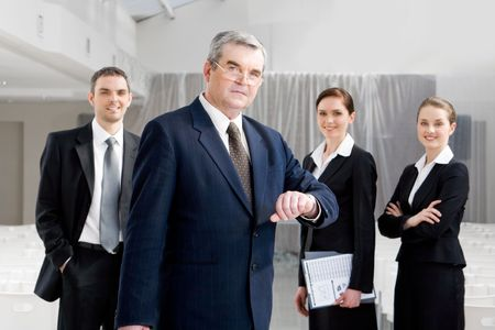 Portrait of senior businessman looking at camera while watching the time at background of confident managers Stock Photo - 4642347