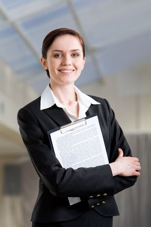 Portrait of pretty female with folder in hands looking at camera with smile photo