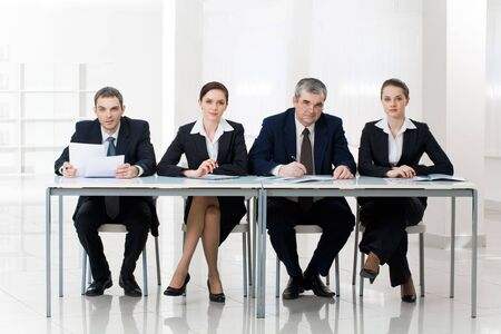 Portrait of smart business people sitting at table and looking at camera