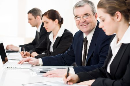 briefing: Confident businessman looking at camera among his employees at briefing Stock Photo