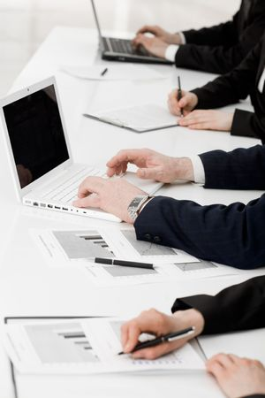 briefing: Image of row of people hands writing on papers and typing at briefing Stock Photo
