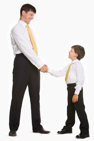 handshaking: Portrait of father and son standing and handshaking while looking at each other on white background